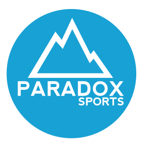 "A blue circle with the outline of a mountain in white with ""Paradox Sports"" written in white."