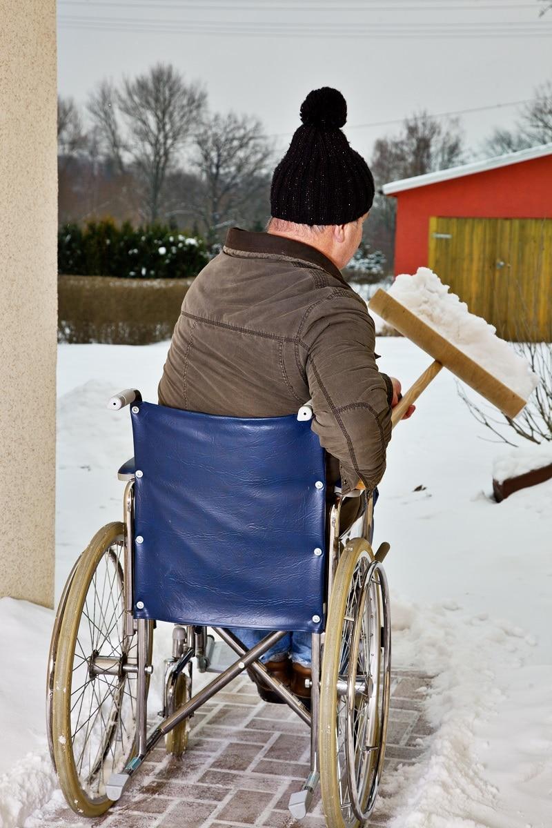 Mann im Rollstuhl beim Schnee schieben