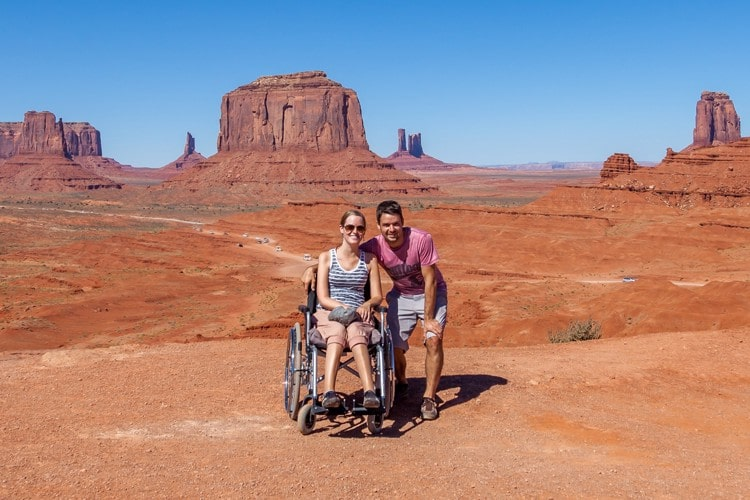 Bibi in a wheelchair and her boyfriend standing by her side in Monument Valley Navajo Tribal Park with rock formations in the background.