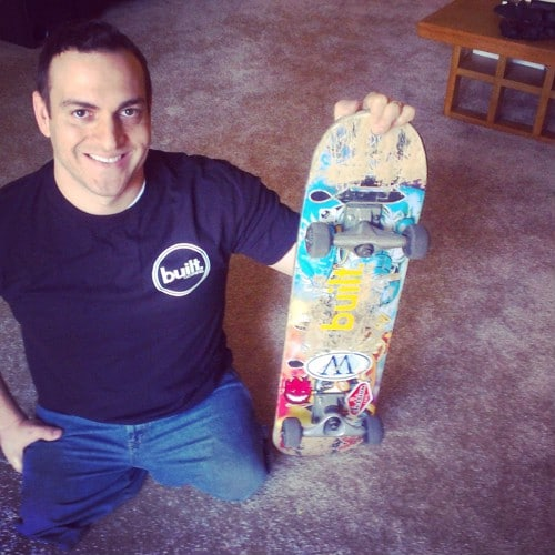 Pace sitting on ground holding skateboard.