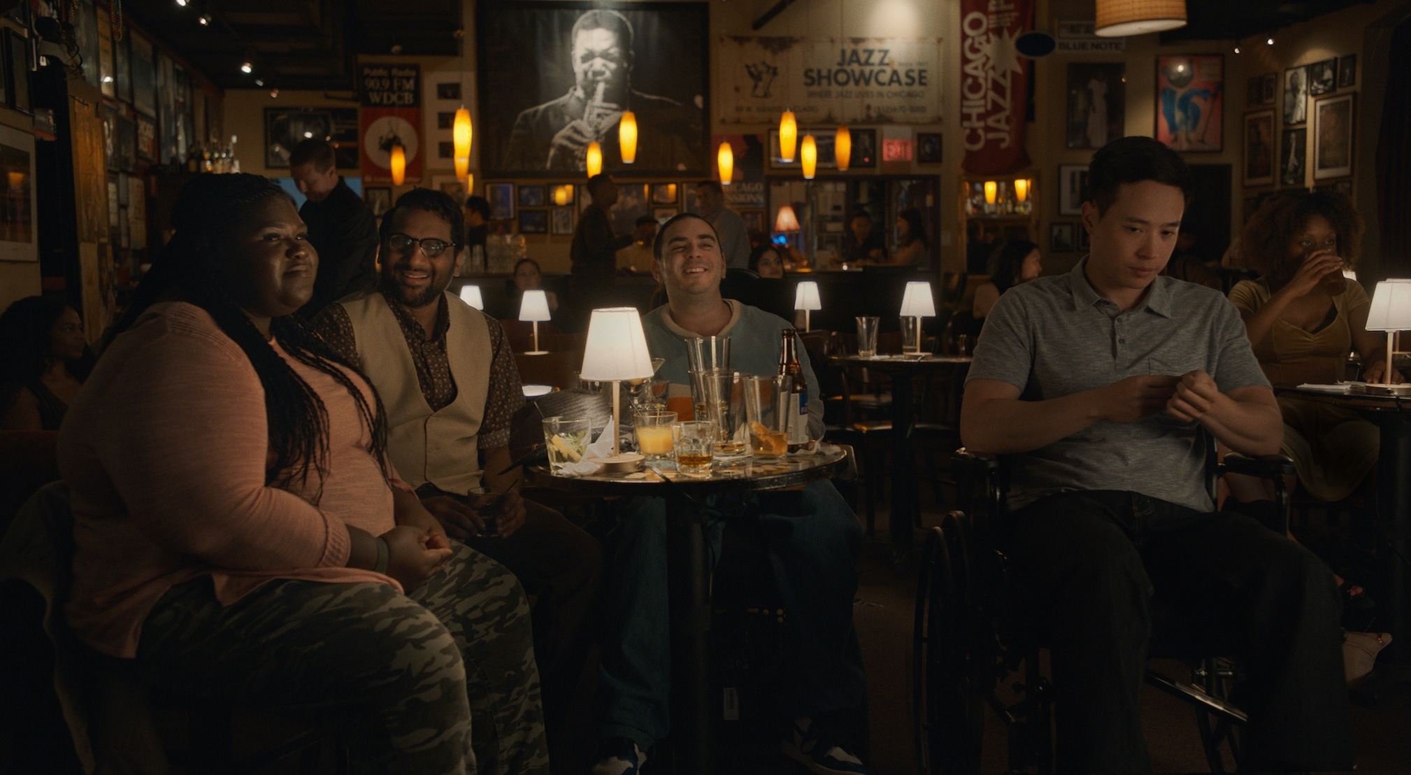Cast of Come As You Are in bar seated around a table