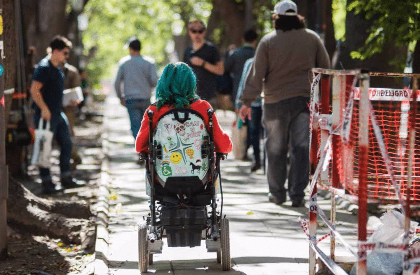 Juana, a young woman with blue hair in her power wheelchair rolling down a city sidewalk