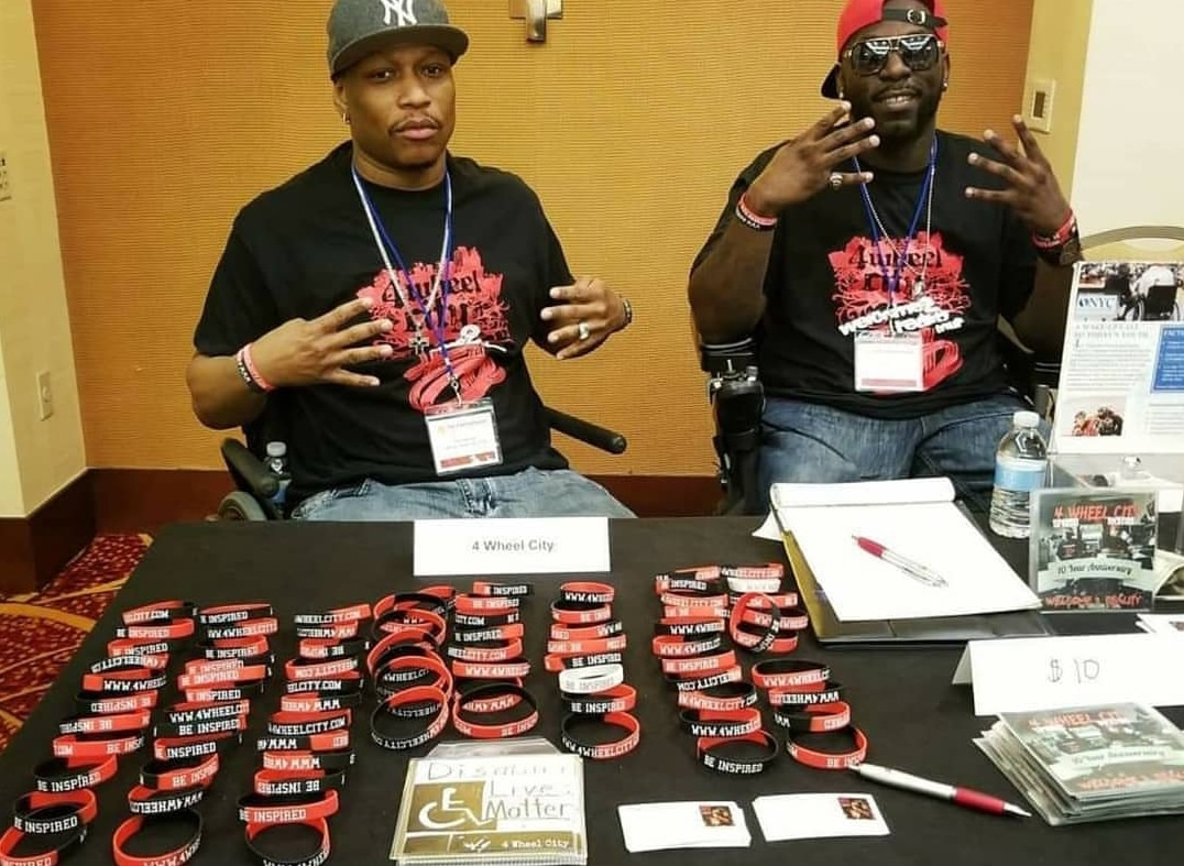Rick Velasquez and Namel Norris (4 Wheel City) sitting behind table selling 4 Wheel City bracelets and CDs