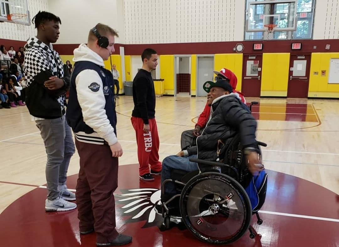 Rick & Namel talking with three male high school students in school gym