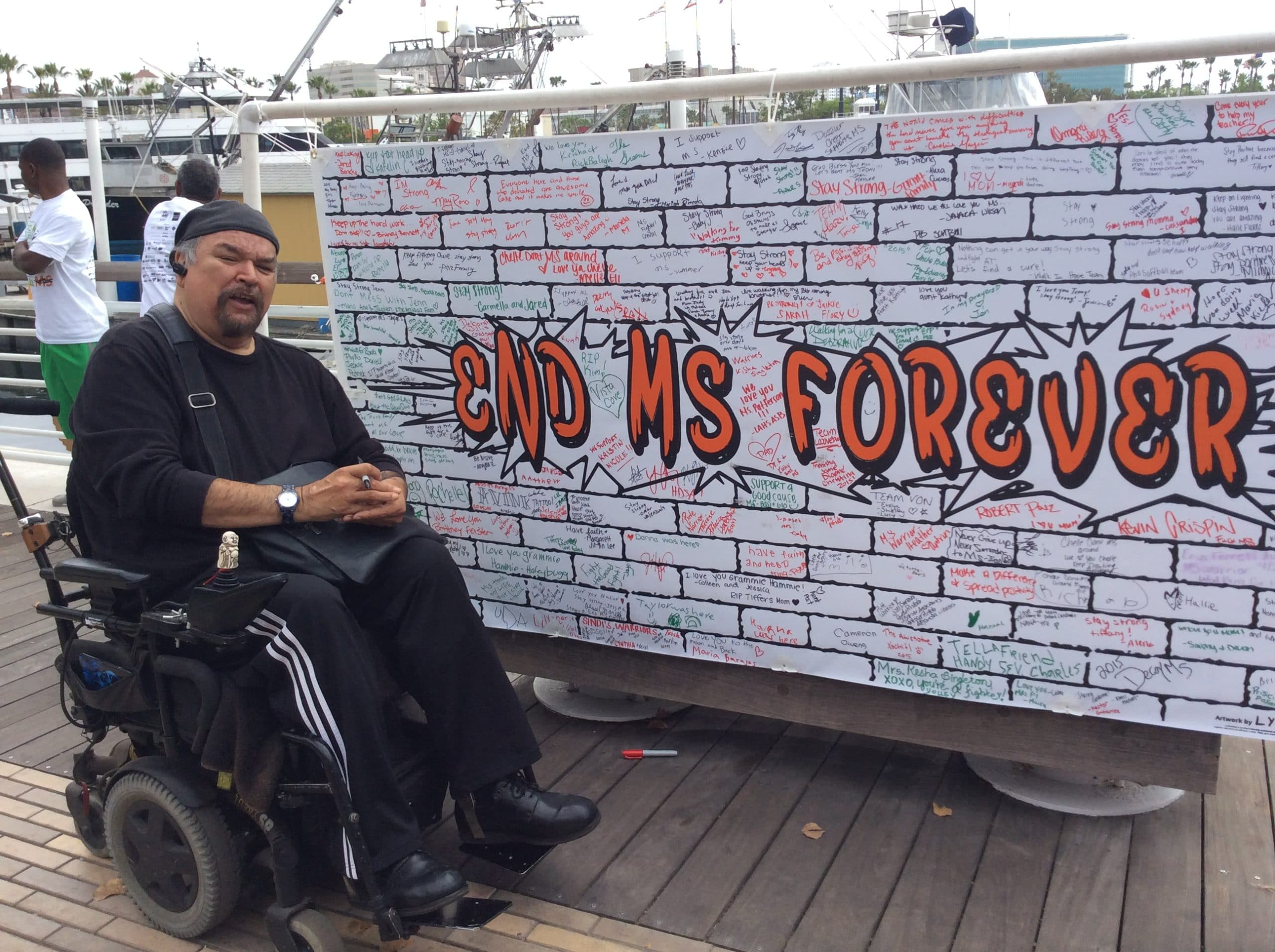"""Carlos by a sign that says """"End MS Forever"""""""