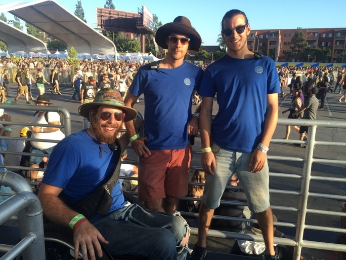 Three Accessible Festivals staff members in blue shirts, one in a wheelchair, two standing at an outdoor event venue
