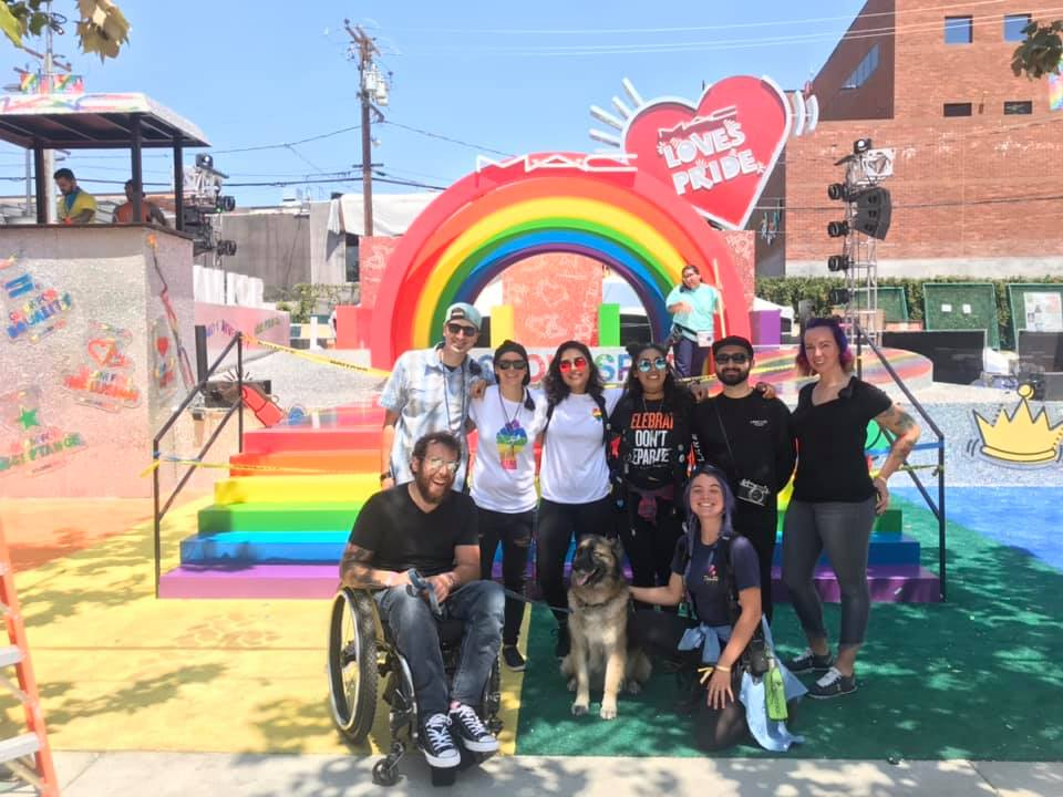 """Group of people, one in wheelchair and one with a service dog, in front of a rainbow display with a """"MAC Loves Pride"""" sign."""