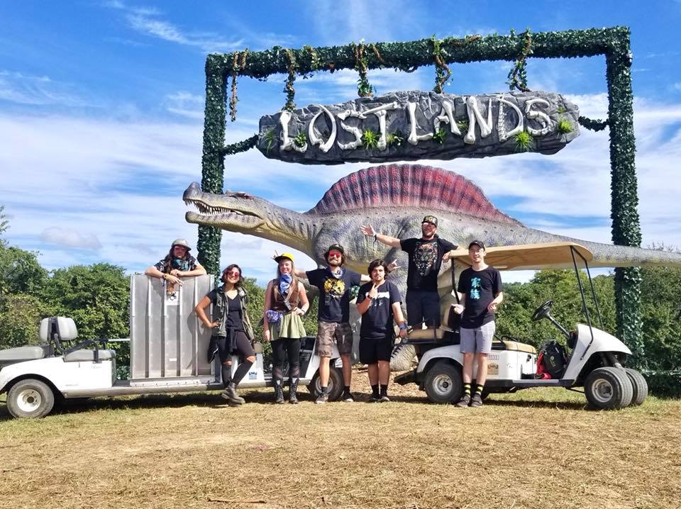 Accessible Festivals crew with golf carts in front of Lostlands sign with a dinosaur statue