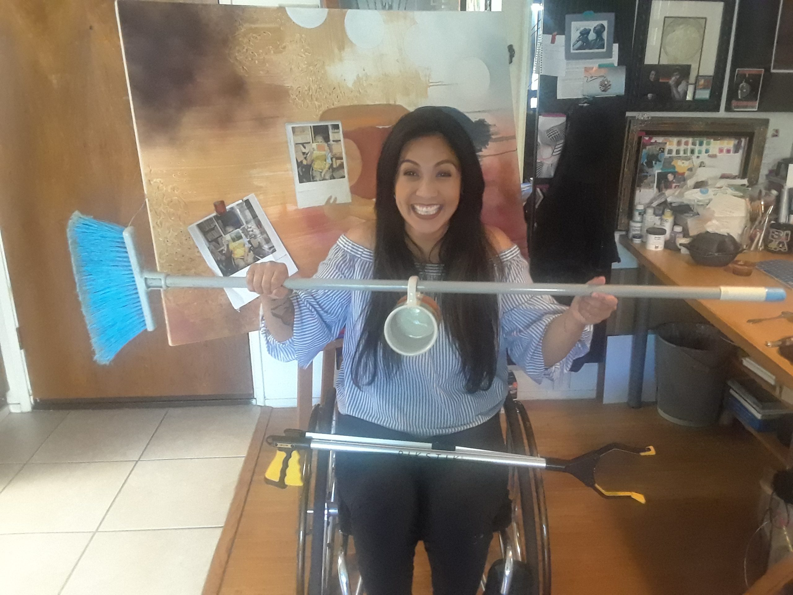 Hydred Makabali in her wheelchair holding a broom with a mug hanging from the stick.