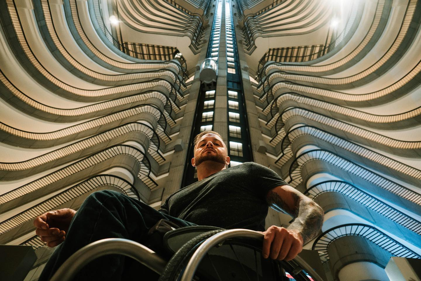 Richard Corbett is in his wheelchair wearing all black. In the background we see a very high building with many stories and an elevator shaft going up the middle.
