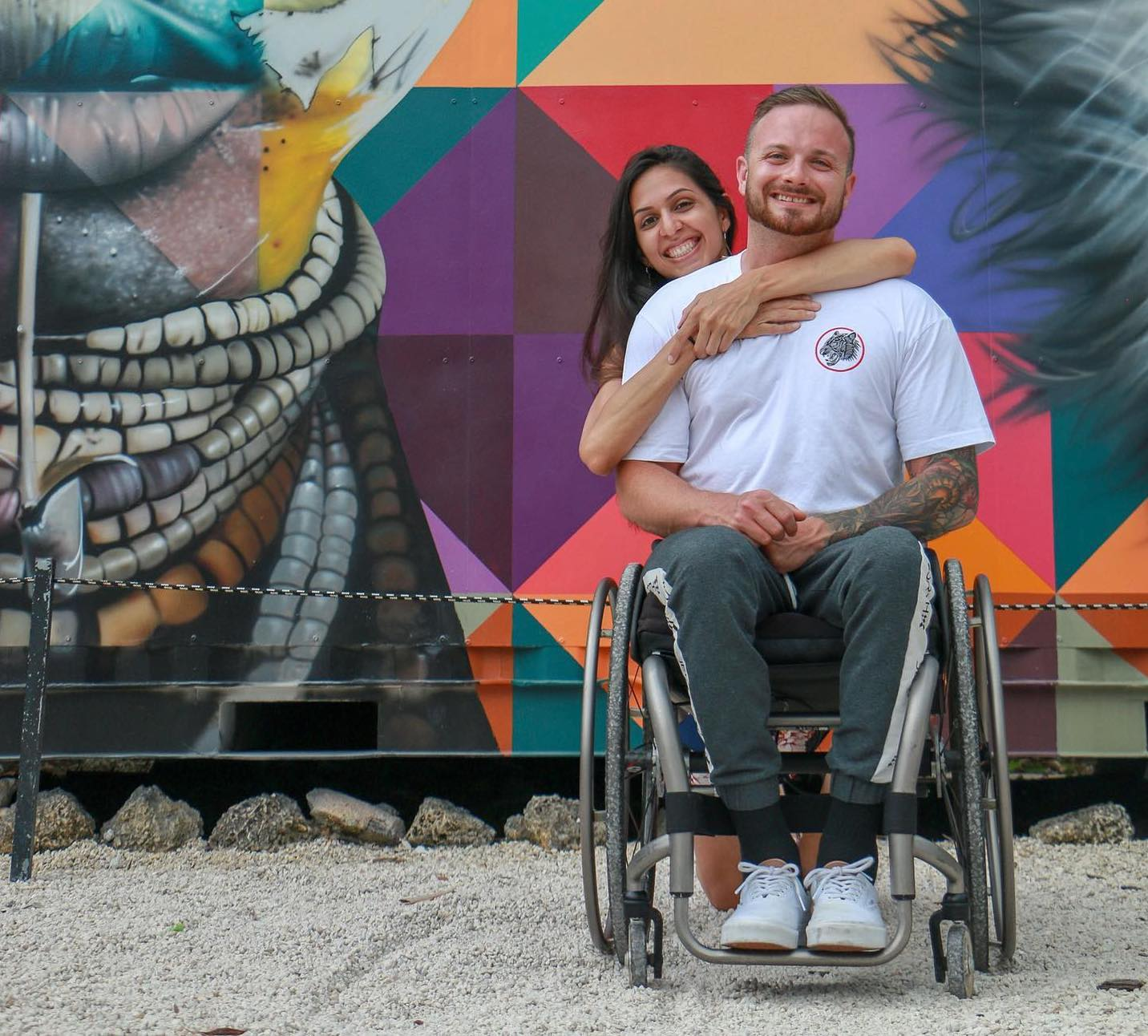 Richard Corbett is sitting in his wheelchair wearing a white t-shirt and jeans. His girlfriend, who has long dark hair, is hugging his shoulders from behind. They are in front of a colorful mural.
