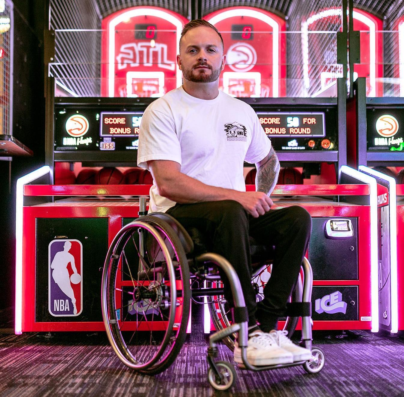 Richard Corbett in a white t-shirt and black pants sitting in his wheelchair in front of some basketball arcade games.