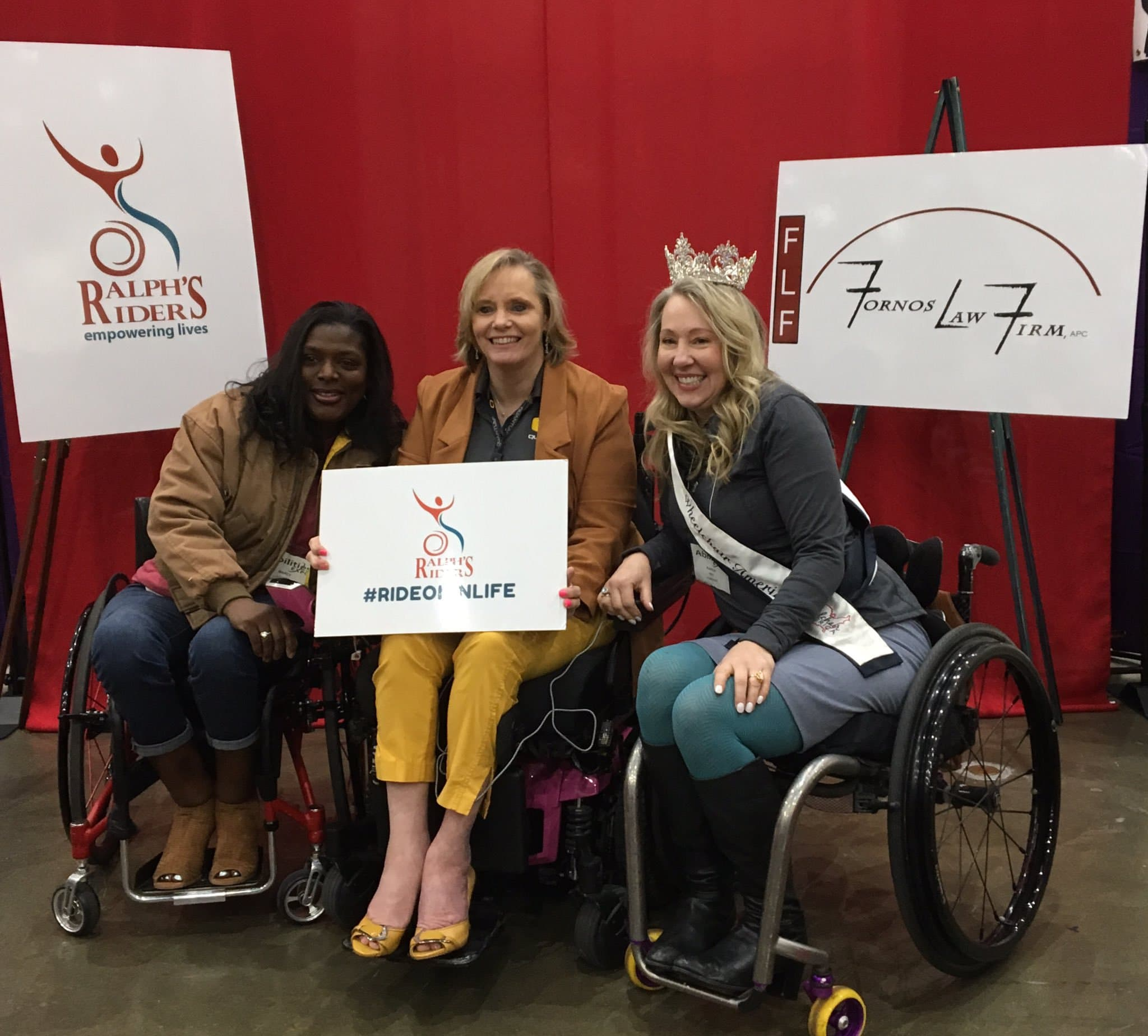 Three women in wheelchairs in front of Ralph's Riders and Fornos Law signs. One is holding a #rideoninlife sign.