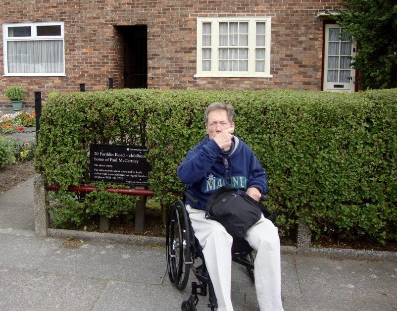 Jim Parsons is sitting in his manual wheelchair in front of Paul McCartney's childhood home in Liverpool, England. It's a brick house with square shrubs in the front.