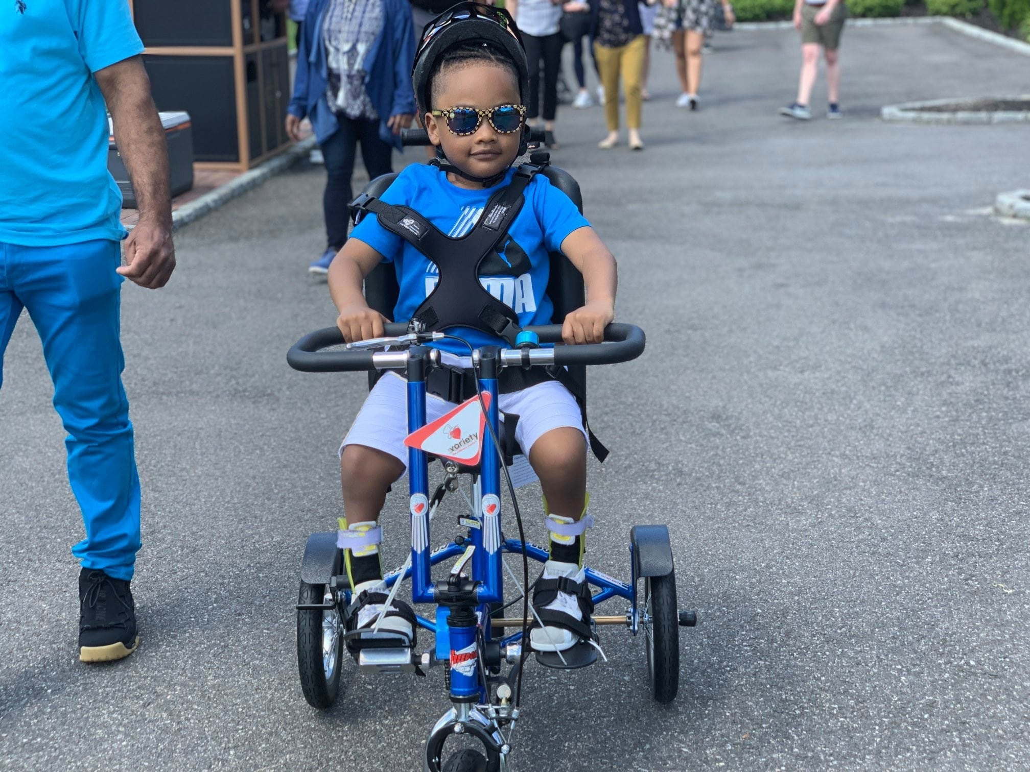 a young boy on his blue adaptive bike