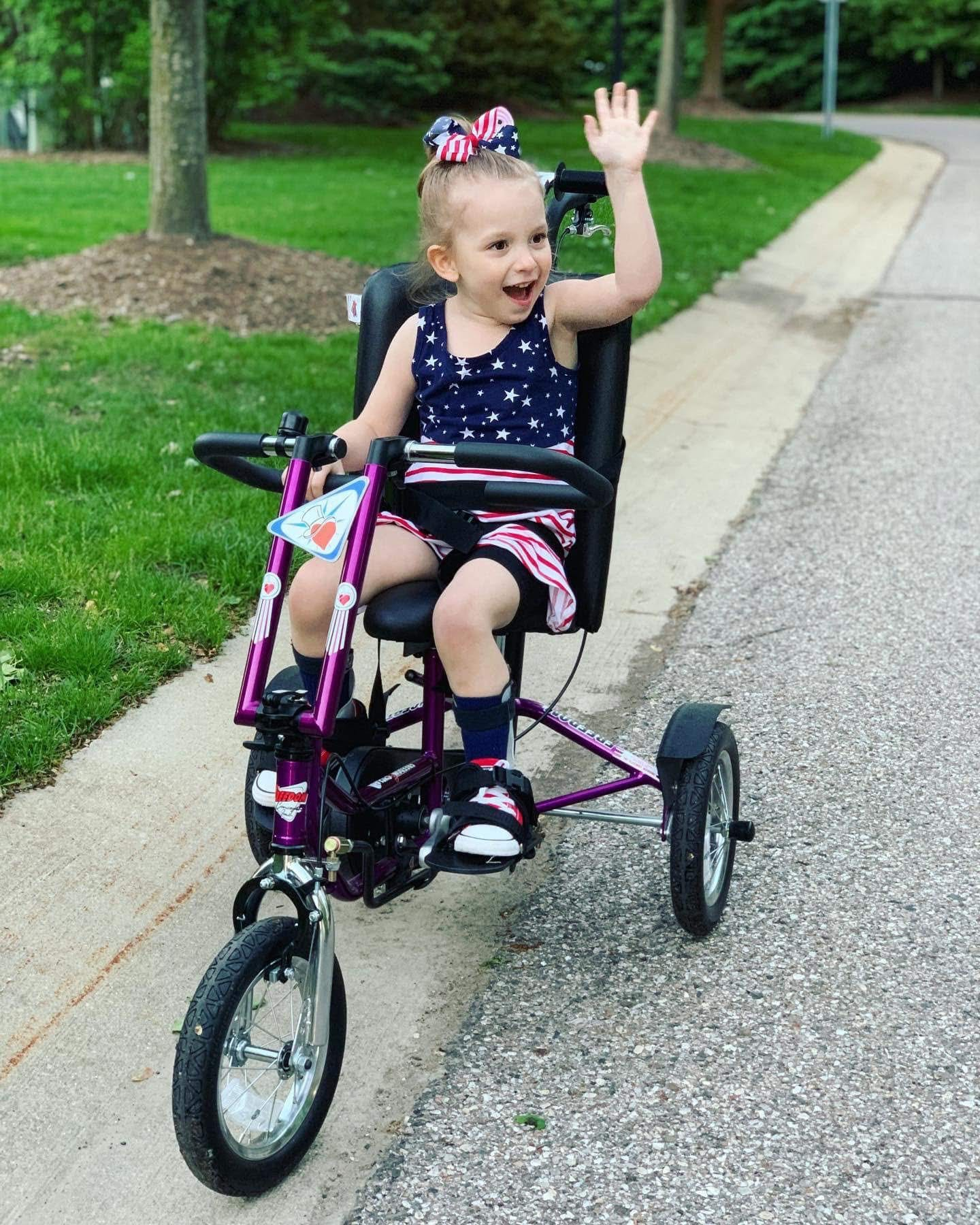 a young girl wearing an american flag-themed outfit on a purple adaptive bike
