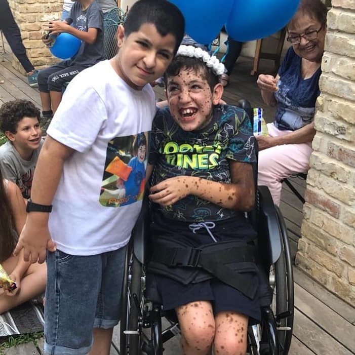 A young boy stands with his arm around Erez who is in his wheelchair. Many children are in the background.