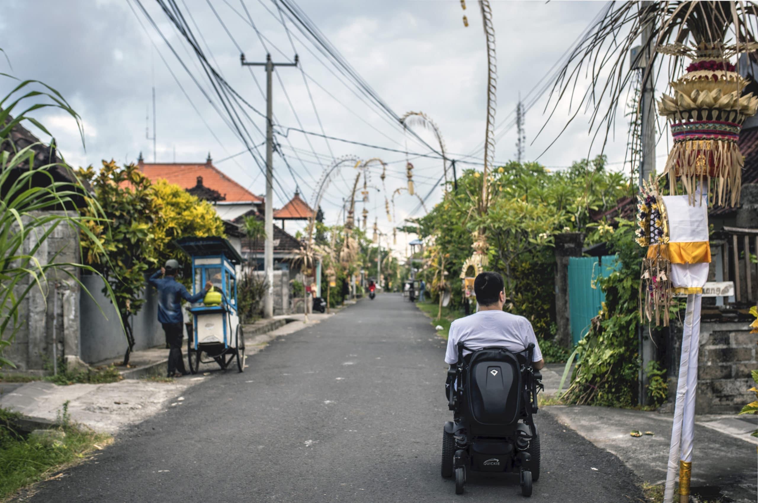 Minna riding down a street in Bali in his wheelchair