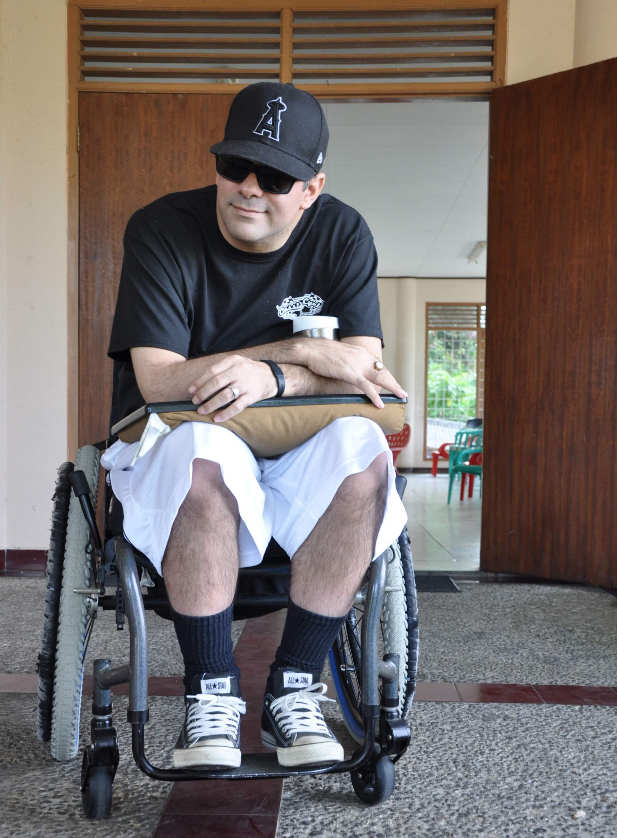 Damien Minna sits in his wheelchair wearing a baseball cap and black sunglasses.