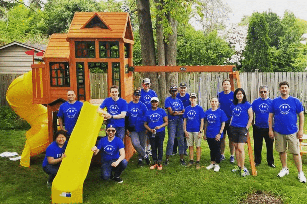 A group of people wearing blue shirts stands in front of a wooden playset with a yellow slide