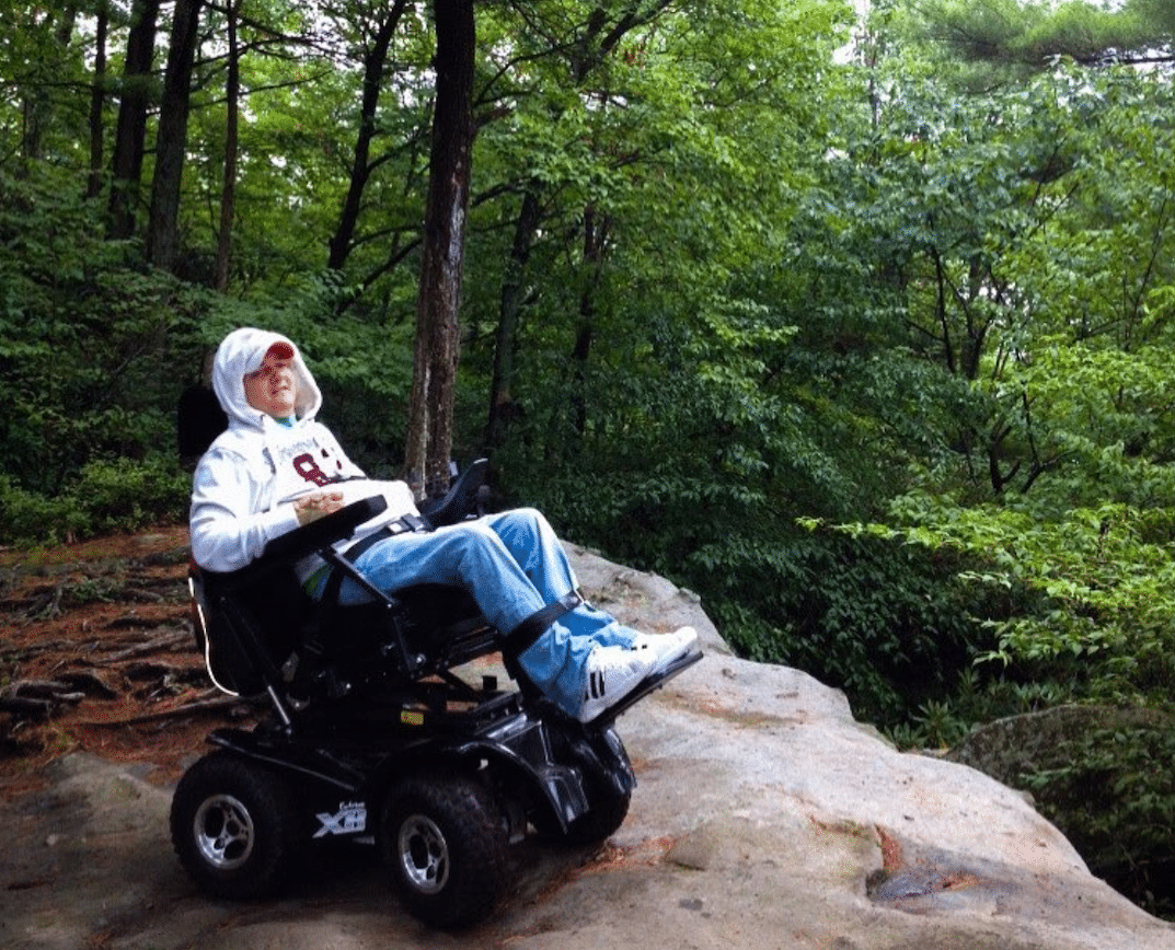 Tim Taylor sits in his power wheelchair on a rocky cliff with green trees in the background.