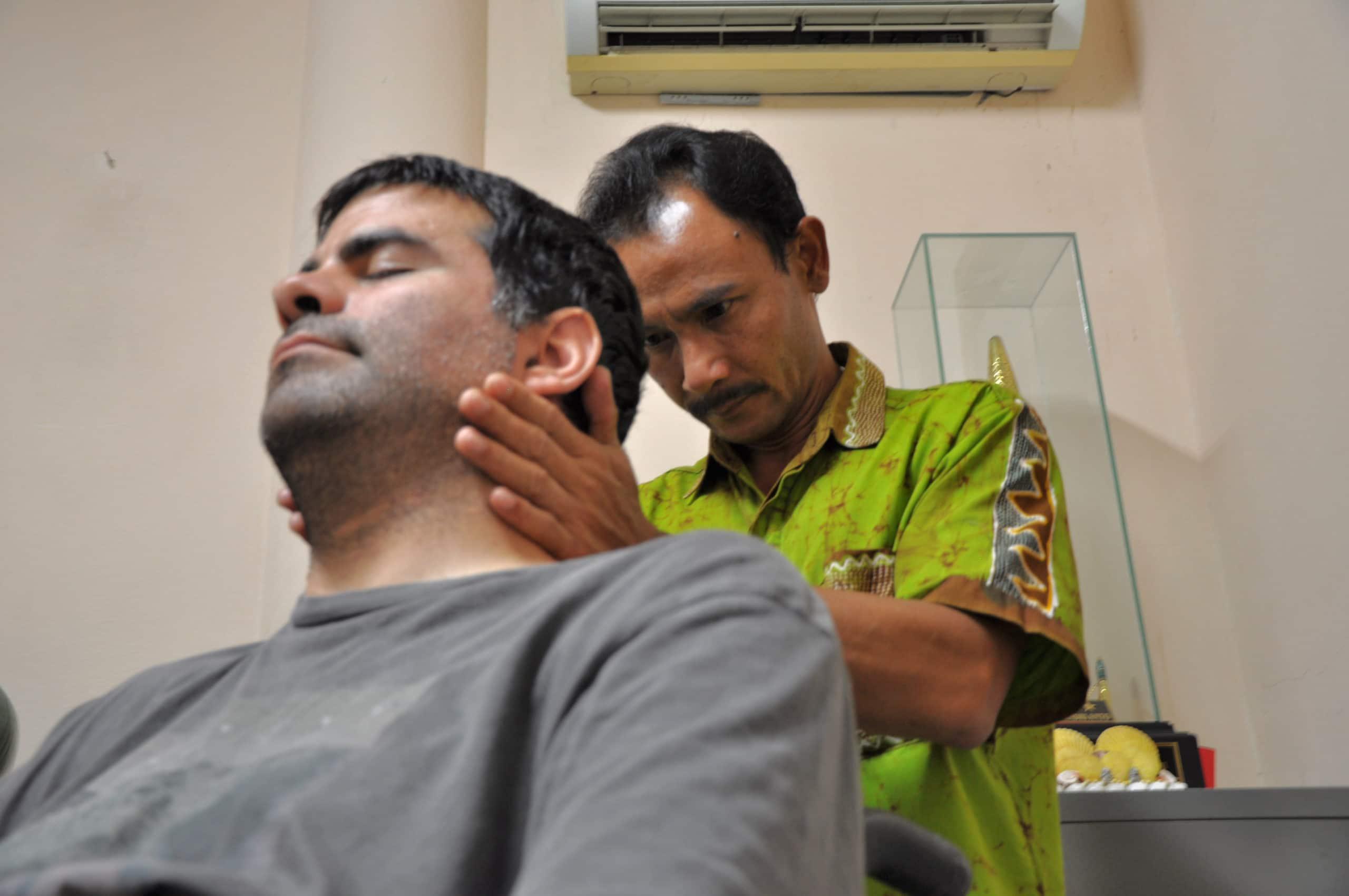 A Shaolin healer works on Minna's neck.