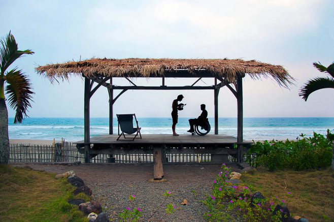 A man standing with a man in a wheelchair under a thatched roof open shelter on a beach.