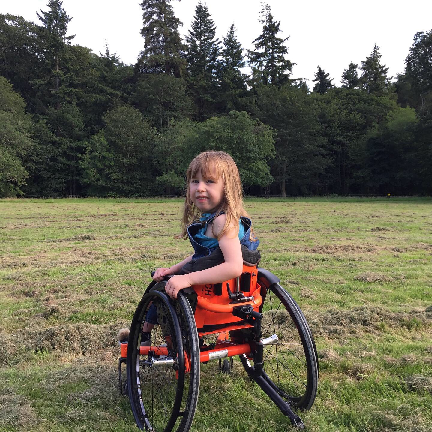 Eudora, a little girl with dirty blond hair, is in a grassy field sitting in her wheelchair looking over her shoulder at the camera.