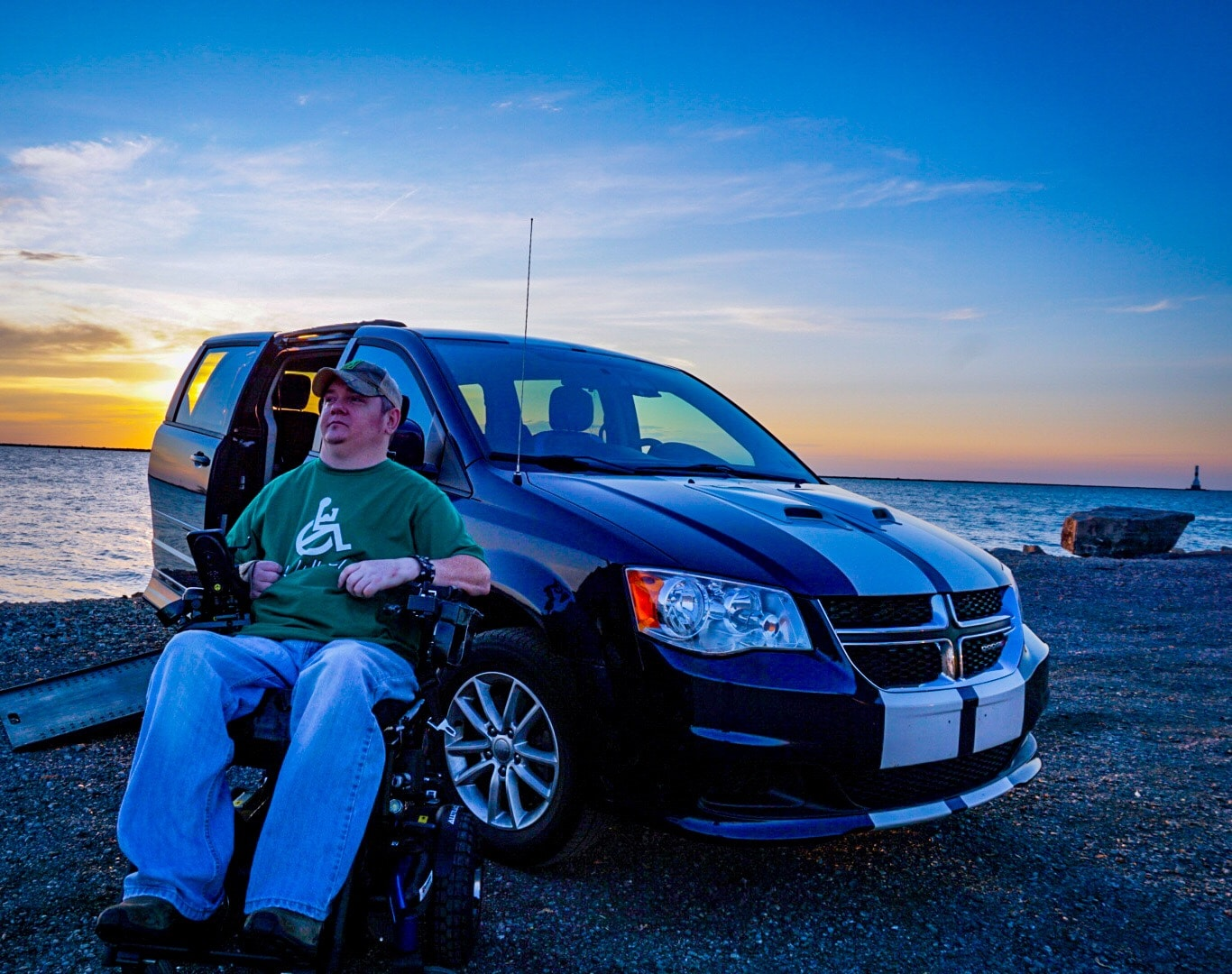 Tim Taylor sits in front of his accessible van. Lake Erie is in the background.