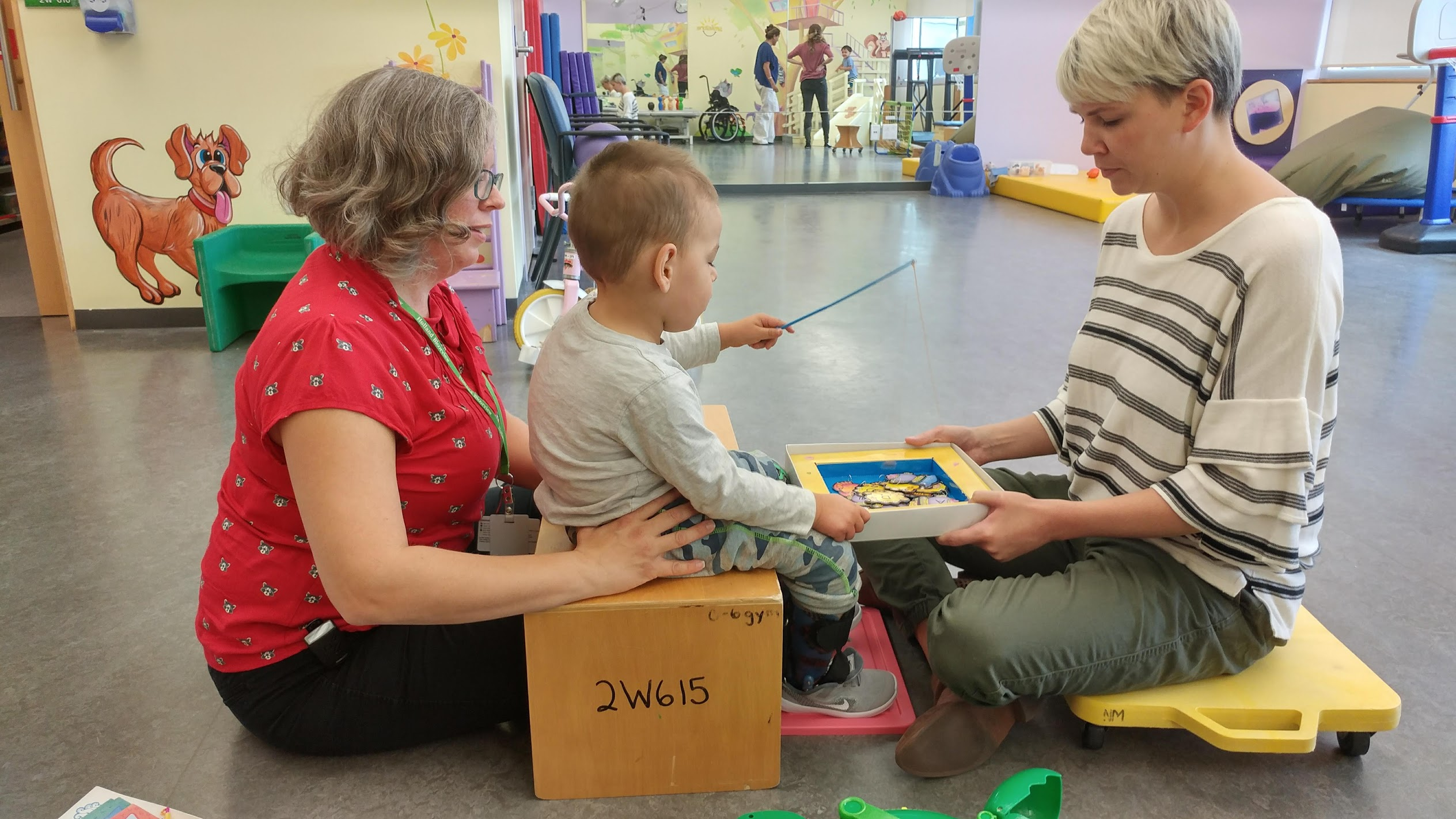 Noah, a little boy, is sitting on a wooden block with a physical therapist supporting his back. Another PT is holding a box while Noah uses a stick to go fishing for items in the box.