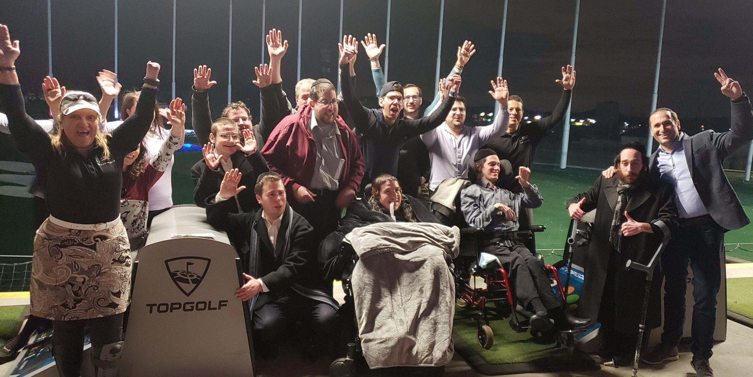 group of adaptive golfers with their hands in the air at a driving range
