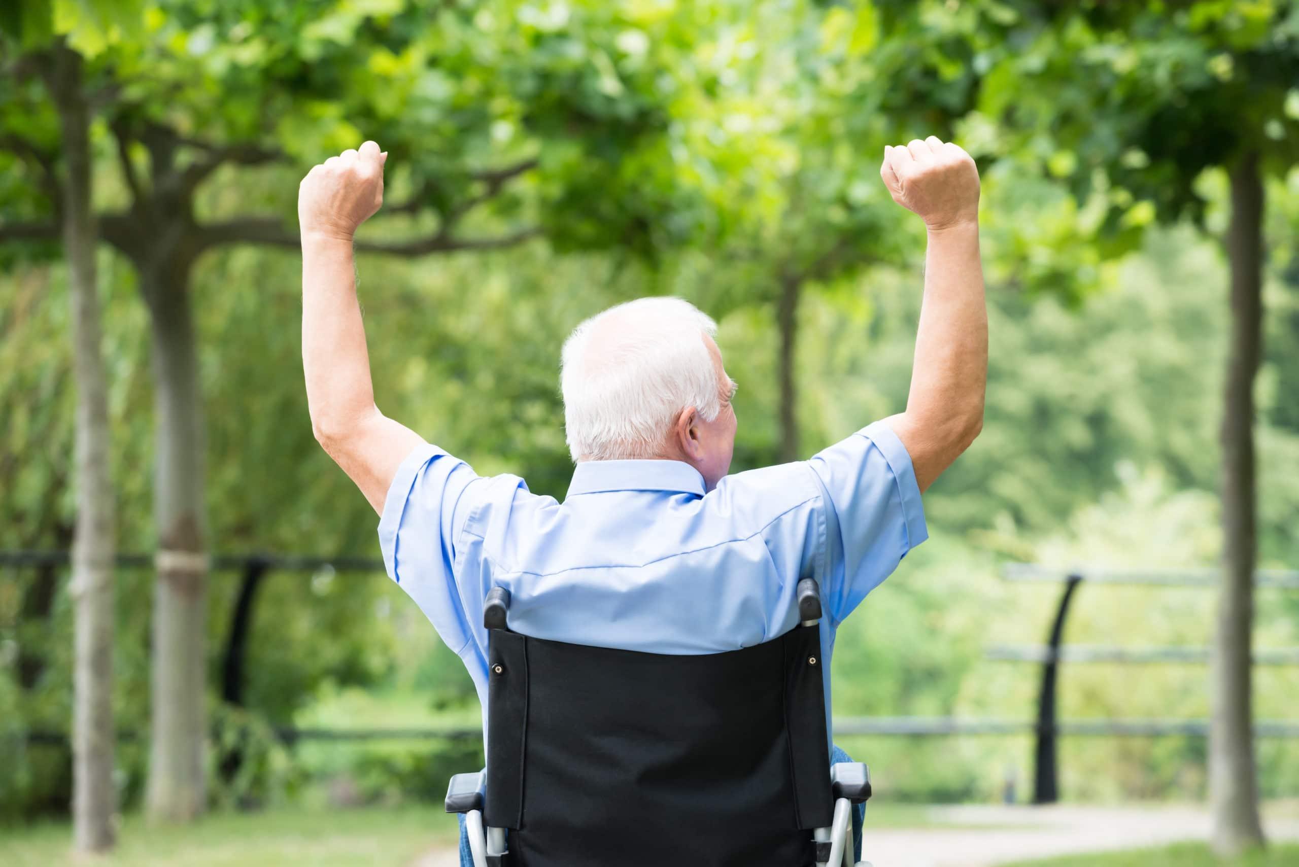 Rear view of a senior man in a wheelchair raising his arms.