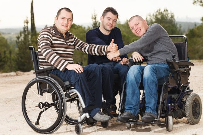 Three young men are sitting outside in their wheelchairs holding their thumbs up.