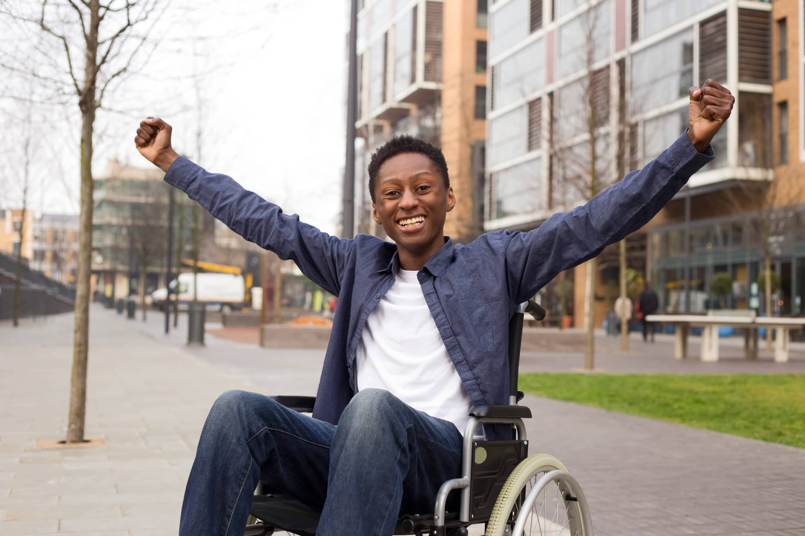 A young man in a wheelchair smiles and holds his arms out.