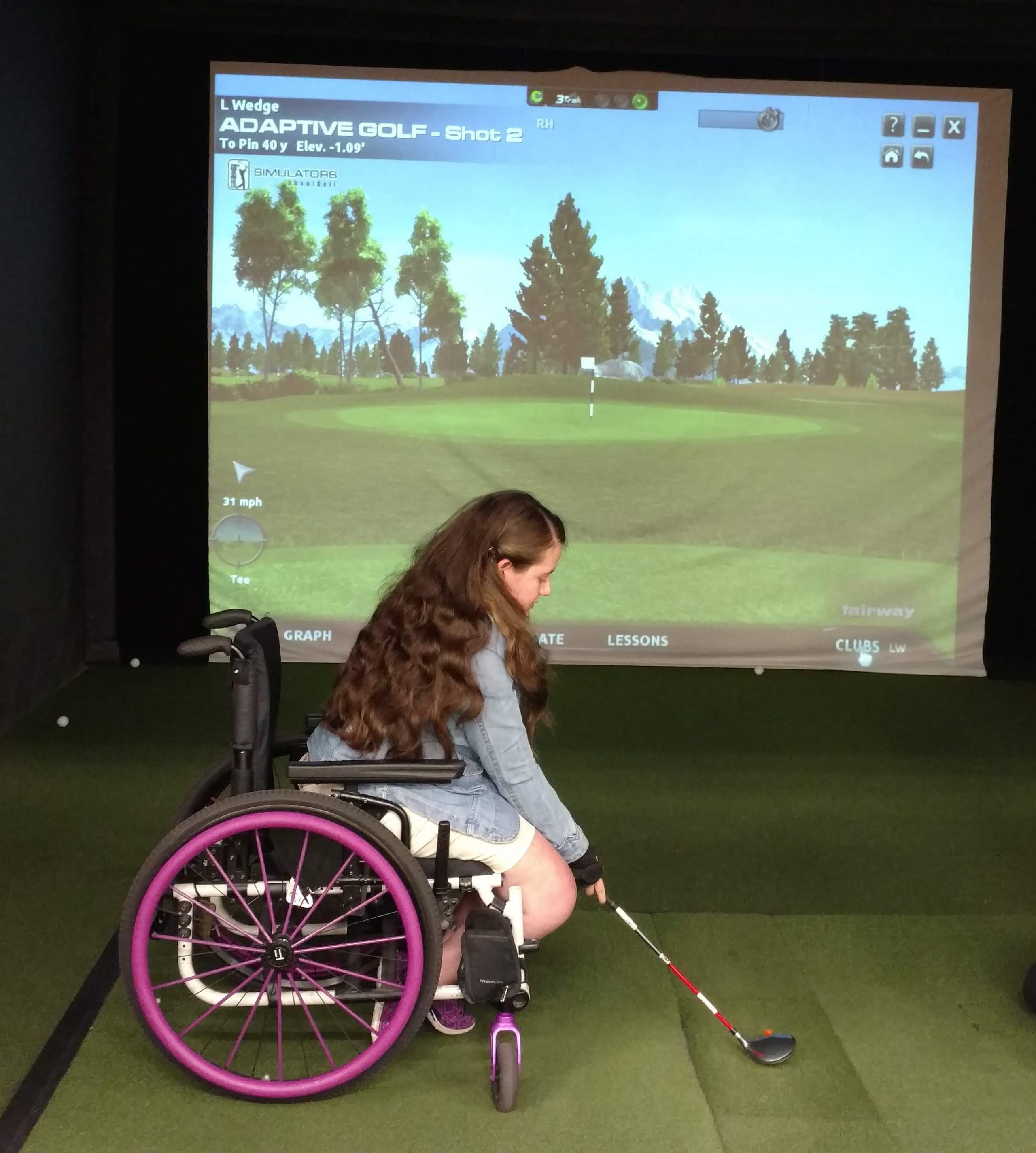 a woman in her wheelchair in front of a golf simulator screen about to swing a club
