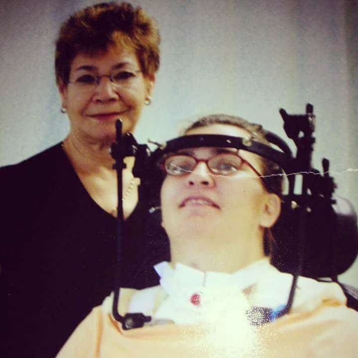 A woman is standing behind another woman wearing a head brace after a spinal cord injury,