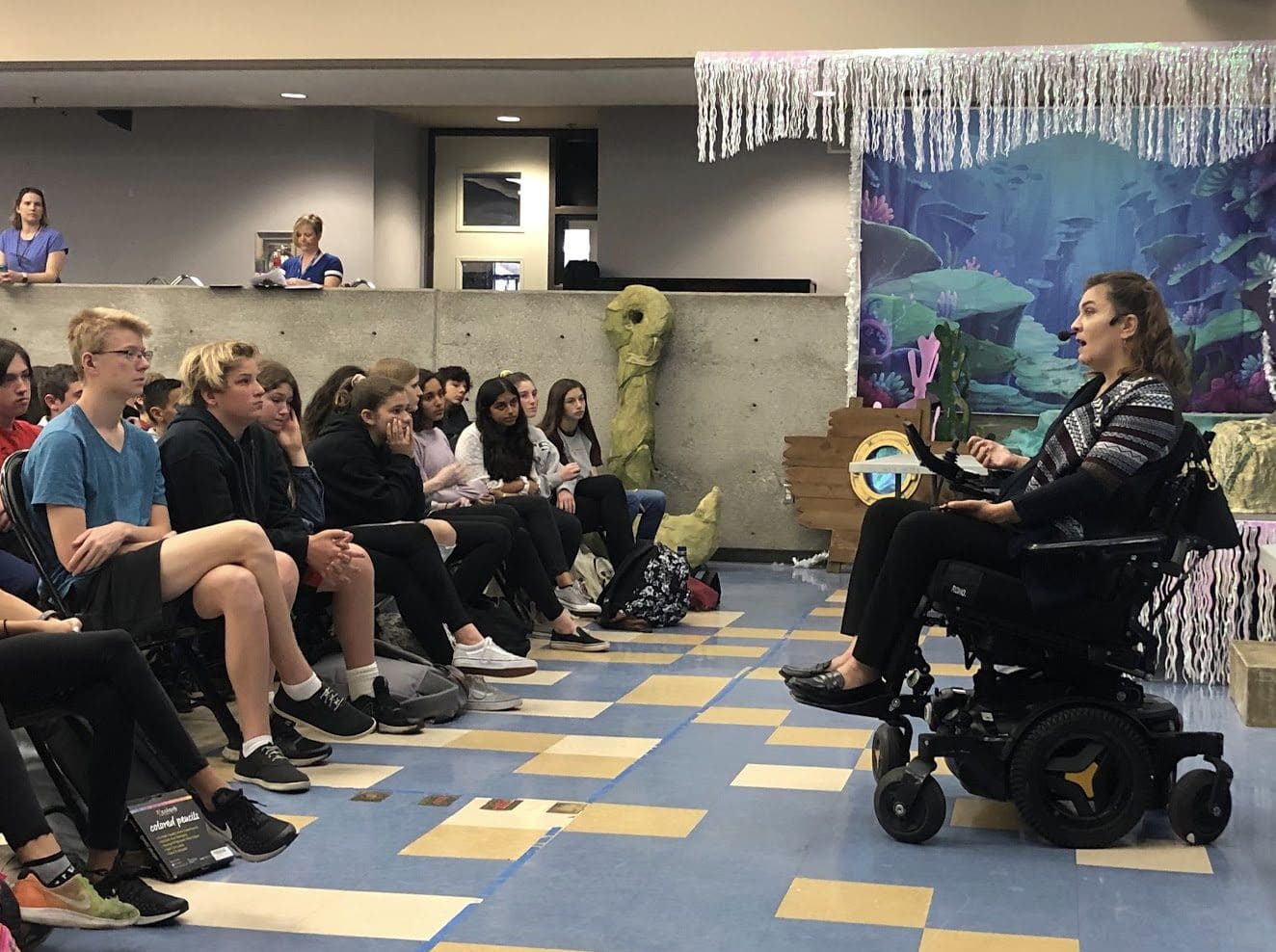 Margarita Elizondo in a power chair addressing a group of students in a classroom.