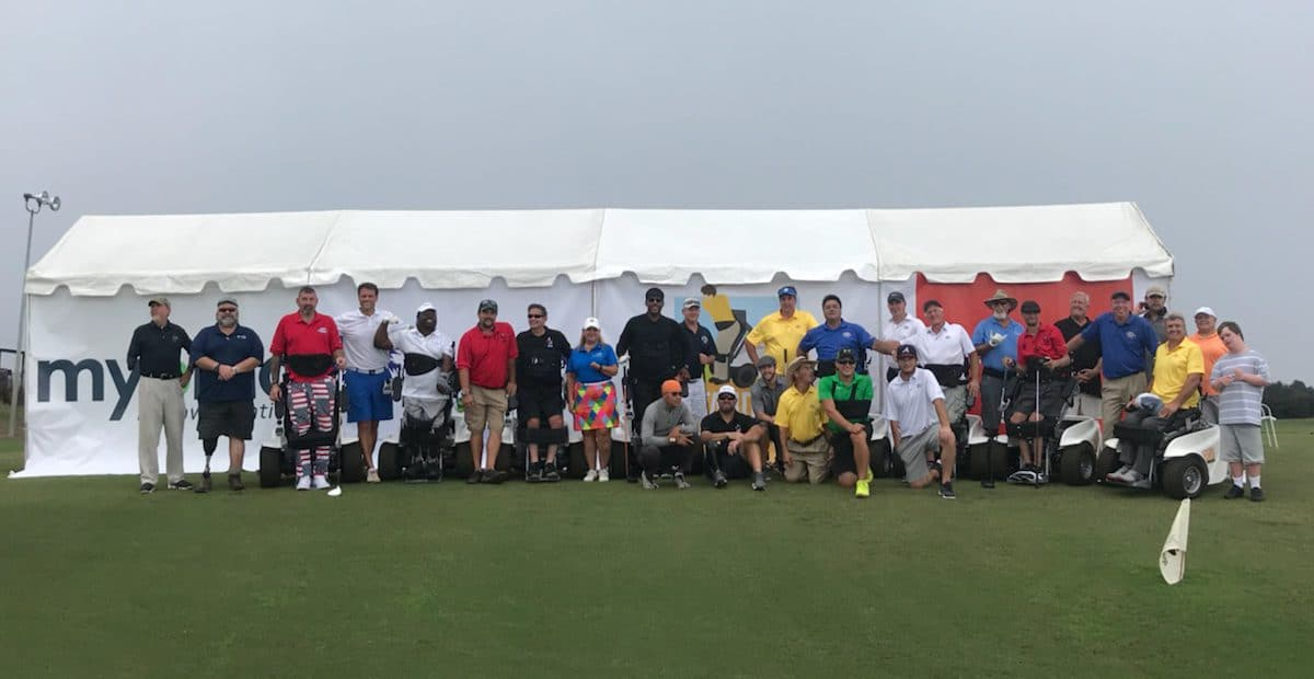 a group of golfers in front of a white tent on a course