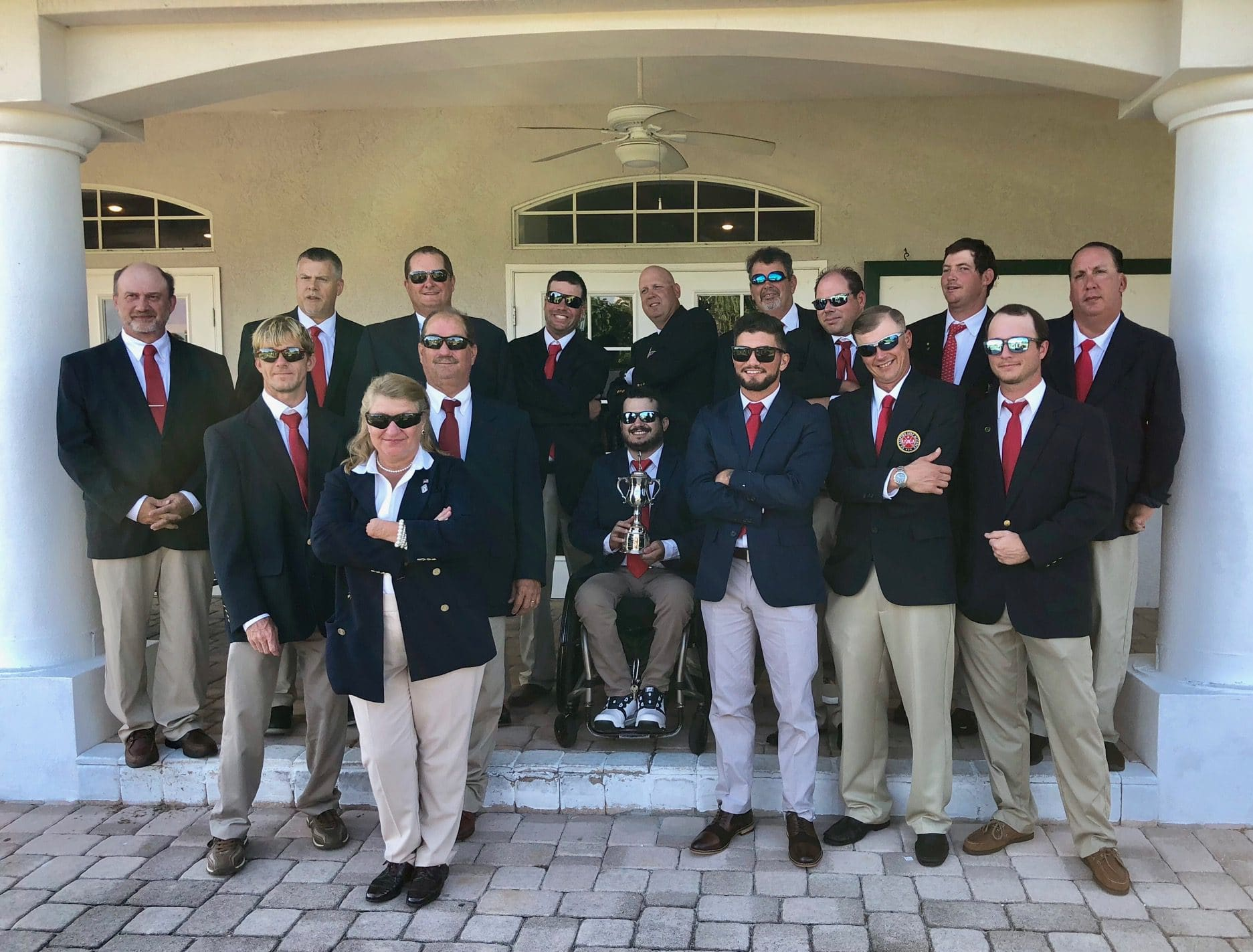 a group of golfers in khakis and black blazers. One is a wheelchair user holding a trophy.