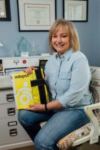 Robin Wearley holds up a package of a yellow ADAPTS sling.