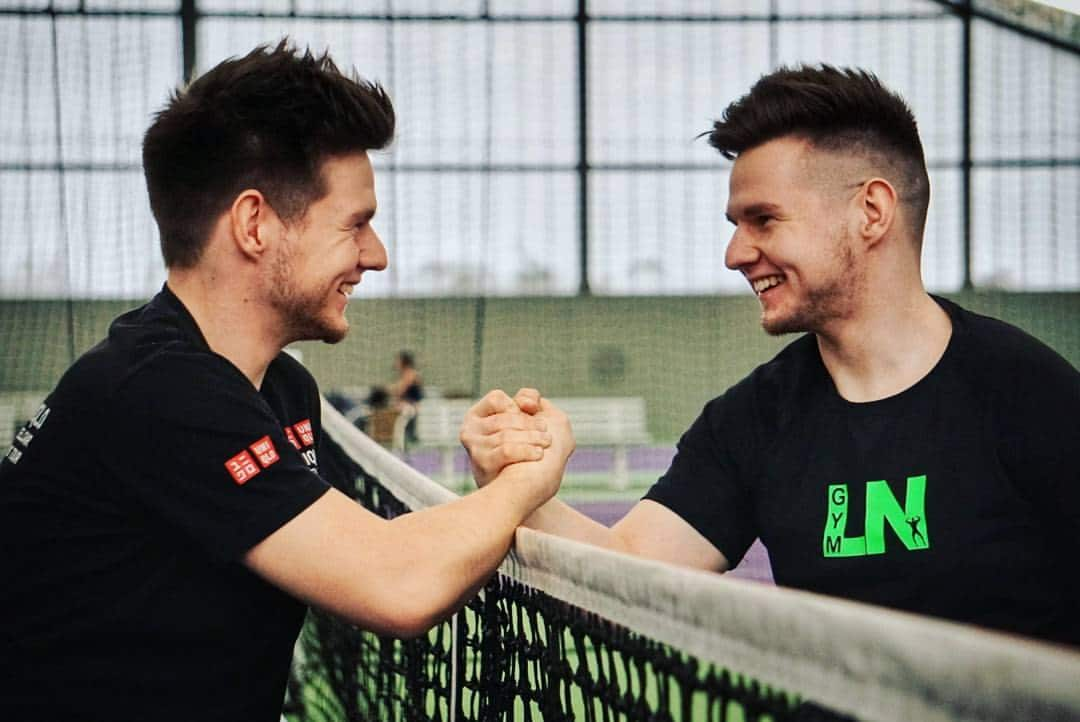 A profile view of twins Max and Marcus smiling and locking hands across a tennis net.