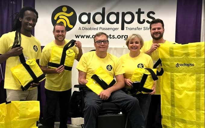 A group of people in yellow t-shirts holding ADAPTS slings.