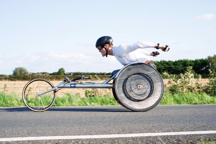 Josh Landmann racing down a street in a racing wheelchair.