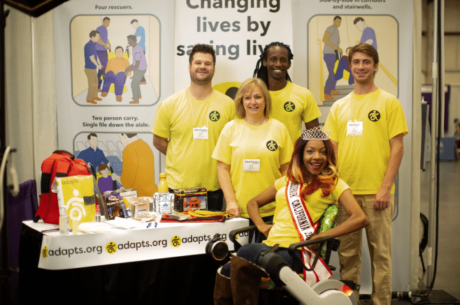 A group of people wearing ADAPTS yellow t-shirts at the booth at Abilities Expo. Ms. Wheelchair California 2018 Krystina Jackson is there with them wearing her crown and sash.