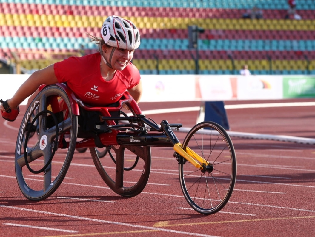 Tanja in a racing wheelchair on an outdoor track. Her arms are back and she's gritting her teeth as if she's pushing hard.