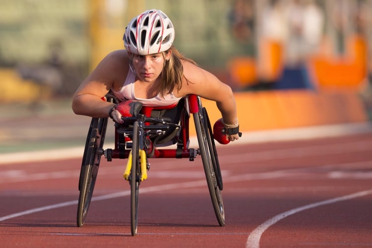 Tanja racing toward the camera on an outdoor track in a racing wheelchair.