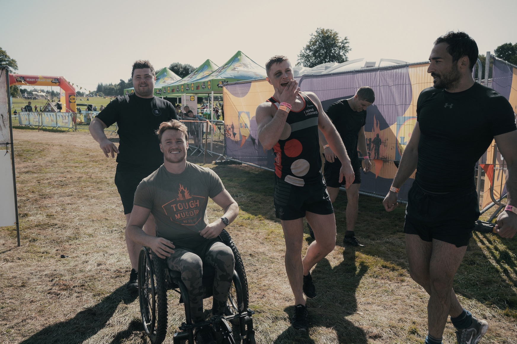 Josh in his wheelchair with four other young men standing around him at a Tough Mudder competition.