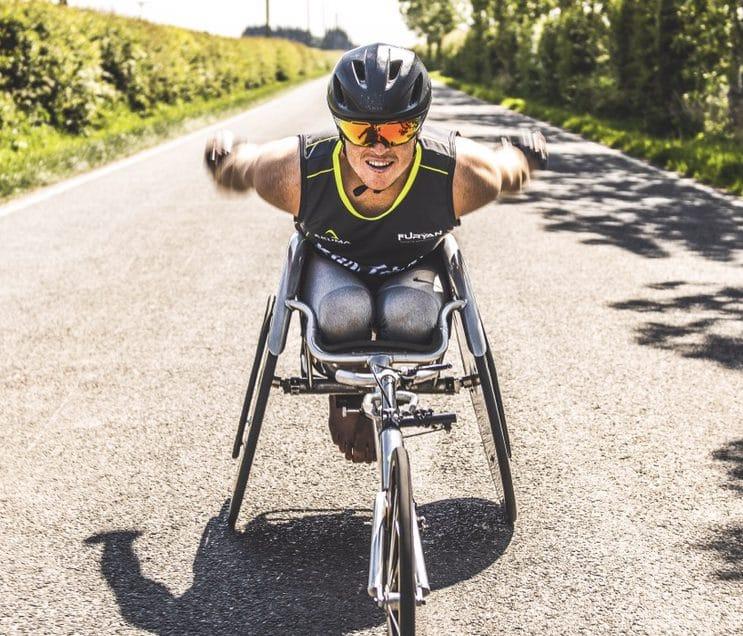 Josh Landmann racing toward the camera in a racing wheelchair.
