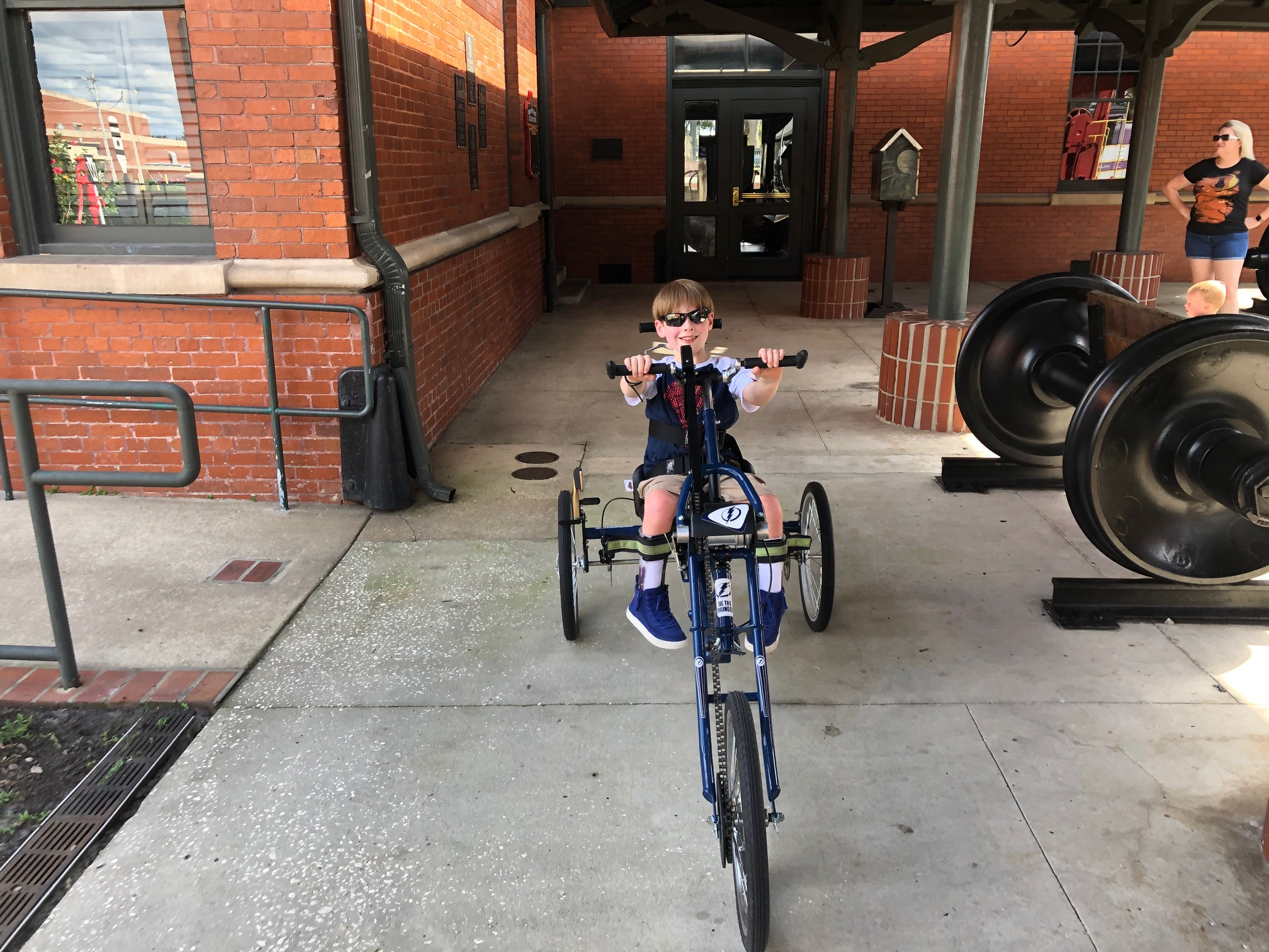 A 9-year-old boy wearing sunglasses riding a three-wheeled handcycle toward the camera.