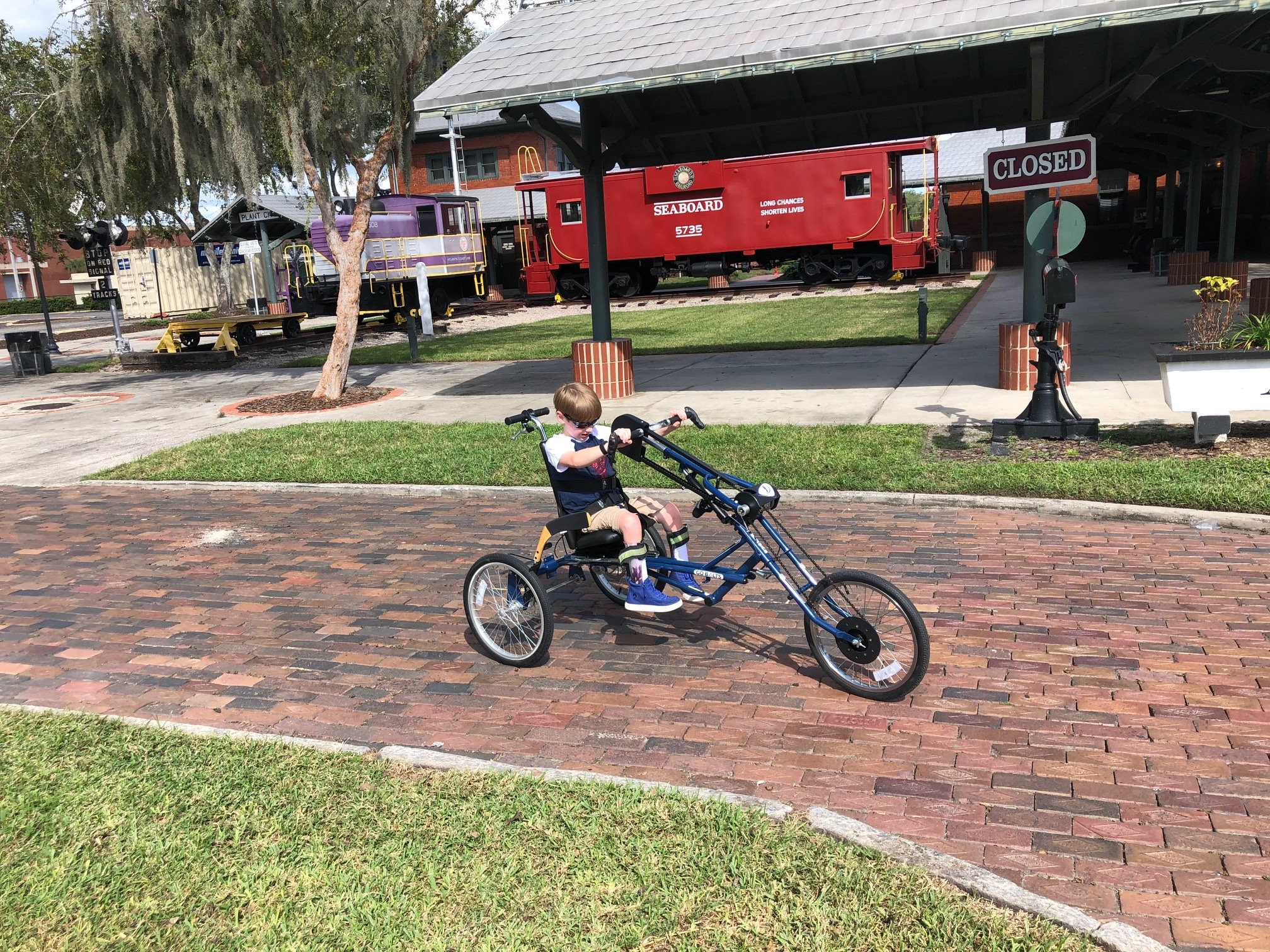 A 9-year-old boy on his three-wheeled handcycle riding down a brick sidewalk with a train caboose in the background.